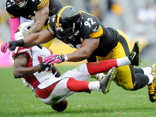 Arizona Cardinals wide receiver John Brown (12) fumbles after being hit by Pittsburgh Steelers outside linebacker James Harrison (92) in the third quarter an NFL football game Sunday, Oct. 18, 2015, in Pittsburgh. (AP Photo/Don Wright)