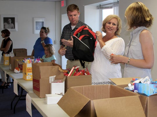 Volunteers fill backpacks with supplies for children in the community as part of the #172vt Back to School Drive.