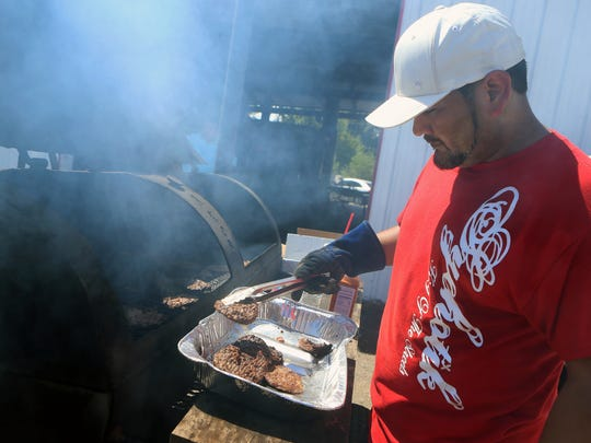 Adrian Rodriguez prepares hamburgers Wednesday, Aug. 23, 2017, at Port A Trim as supporters stand in line to boy meals and to donate money for the funeral expenses of Royalty Coleman, who was killed Monday, Aug. 21, 2017, in a hit-and-run on Everhart Road.