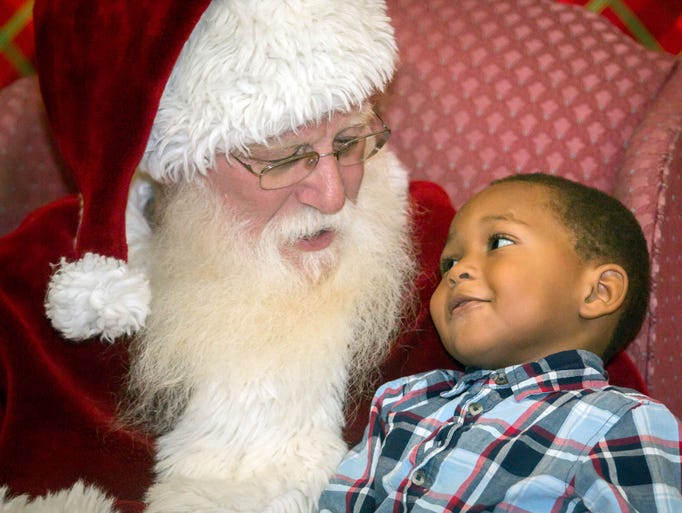 3 year old LaMarion Davenport chats with Santa at the