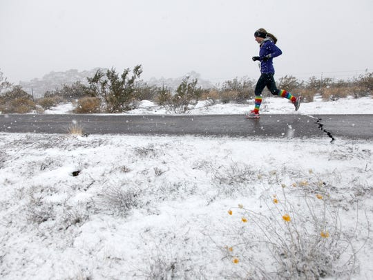 A handful of desert flowers add a note of color to the landscape as a runner braves snow flurries drifting over the trail along state Route 18 as she competes in the Expedition St. George, a 50 mile team really race that winds from the Town Square Park in downtown St. George, up through Snow Canyon State Park, through Washington Fields and back around the Southern Parkway to the Dixie Center Saturday, Dec. 7, 2013. Despite the cold and wintery conditions, 42 teams, most comprised of five team members, competed in the relay race.