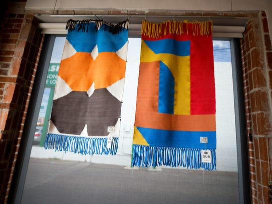 Rugs from Portugal hang in the window of Noons vintage
