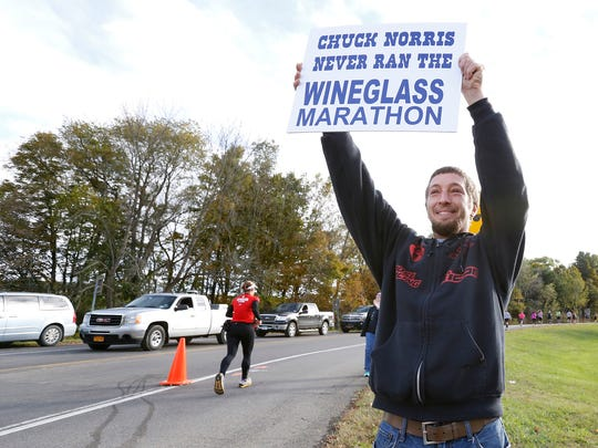 Will Beckhorn, of Addison, cheers on his daughter, Kelly McNamara for her first marathon during the Wineglass Marathon Sunday. Beckhorn said will continue stopping at all viewing spots along the course.
