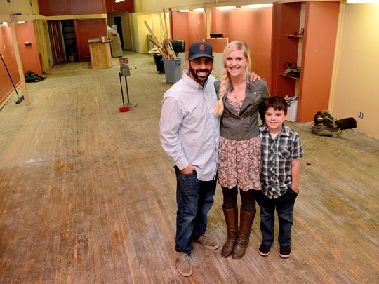 Mark and Krysta McGee, owners of Mark's Dogs, along with their son Christian, 7, stand inside their new restaurant space in Eaton Rapids, Tuesday, November 3, 2015. The McGee's bought the building, that used to house a hair salon, and are in the process of converting it to an eatery.
