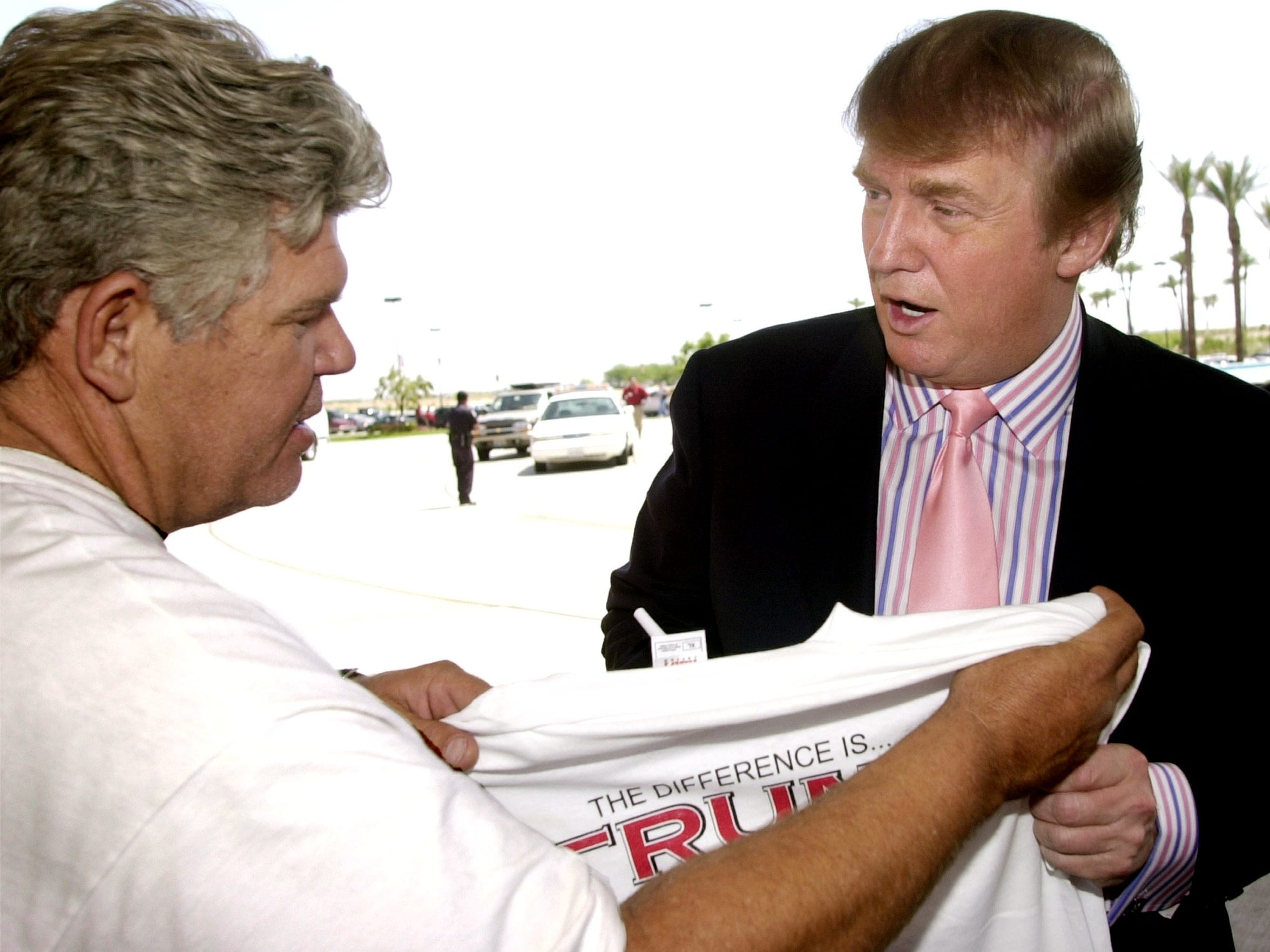Donald Trump puts his autograph on a t-shirt after stepping out of his limo at Trump 29 in 2004.