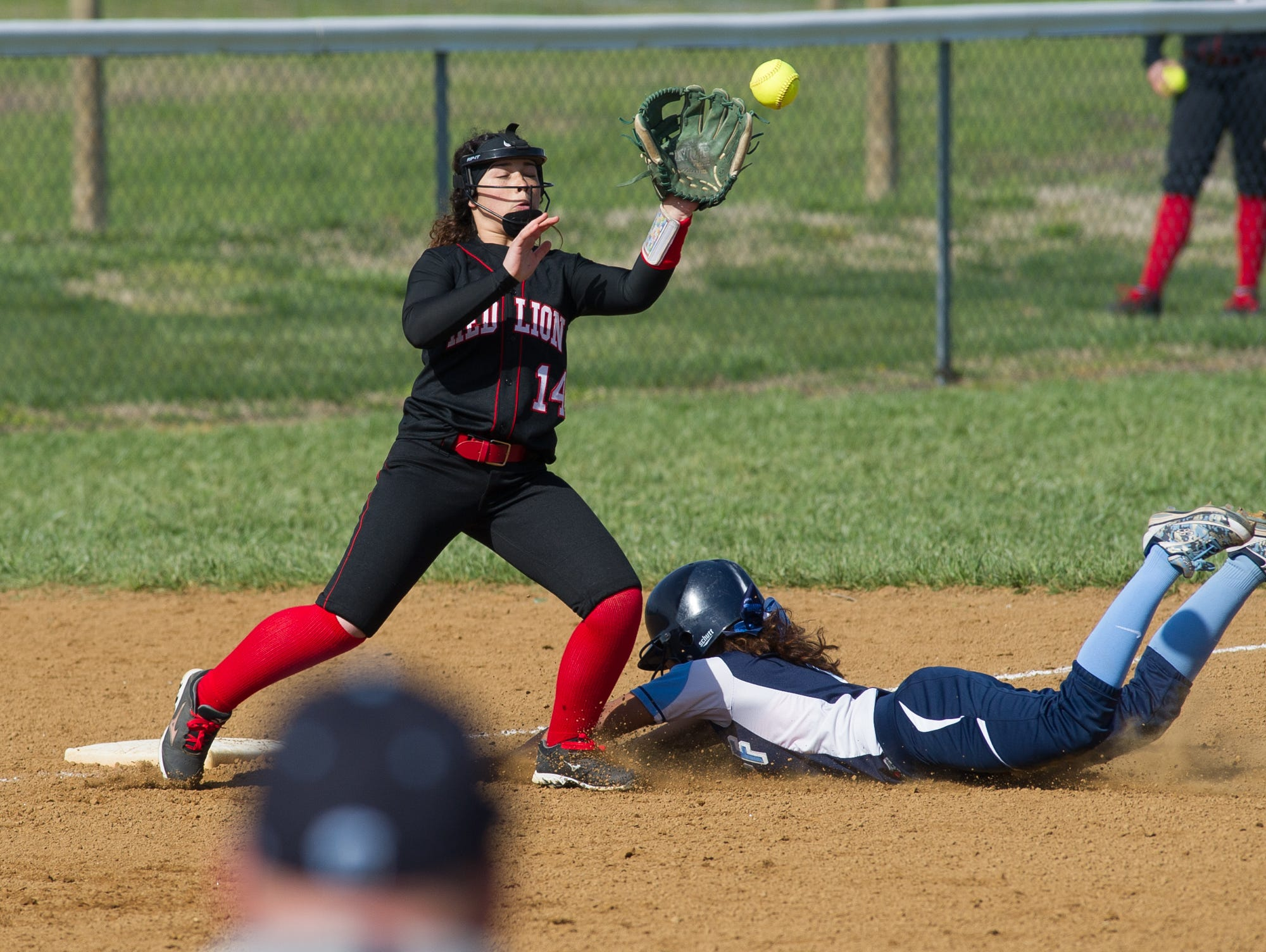 Red Lion's Gabriella Lano (14) attempts to tag out Lake Forest's Mya Maddox (1) at third base.