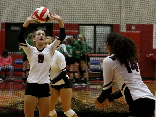 Vernon's Taylor Reeves sets the ball for Cameron Garza