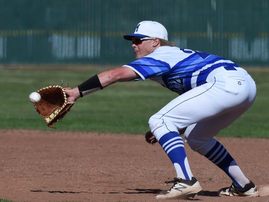 McQueen's Mason Winship gets the out at first against Reno's during Thursday's game at McQueen High School.