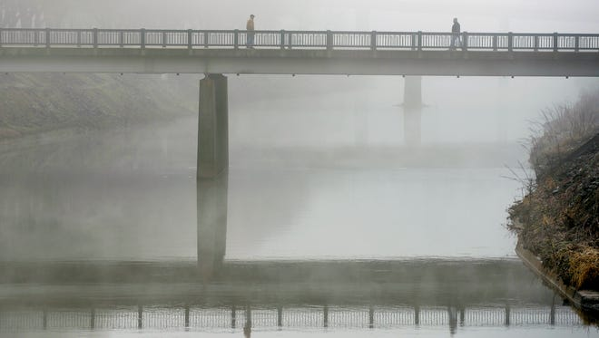 Two people walk the Princess Street bridge across the Codorus Creek in York amid a dense fog advisory in 2014.