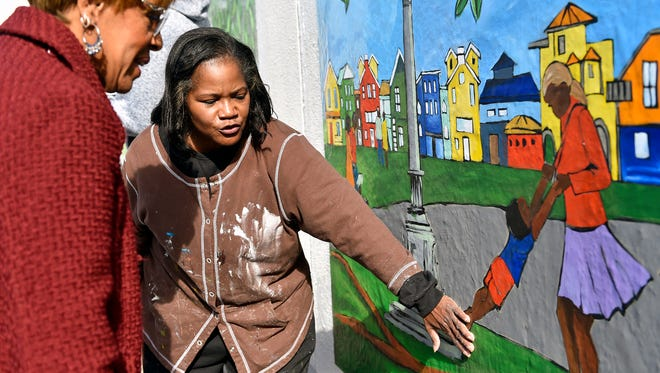 """Ophelia Chambliss talks with state Rep. Carol Hill-Evans about the new """"York Community of Color"""" mural on the side of the Voni B. Grimes Gym. The artist designed the six panels of the mural, which about 200 members of the York community painted over a period of three months."""