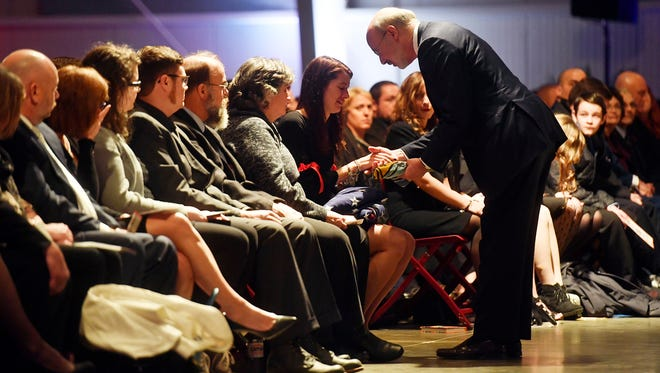 Pennsylvania Gov. Tom Wolf presents a state flag to York City firefighter Zachary Anthony's widow, Brooke, during a public memorial service honoring him and fellow firefighter Ivan Flanscha on Wednesday, at the York Expo Center. Flanscha and Anthony were killed in the line of duty on March 22, while containing hot spots the day after a three-alarm fire consumed the old Weaver Organ and Piano building in York.