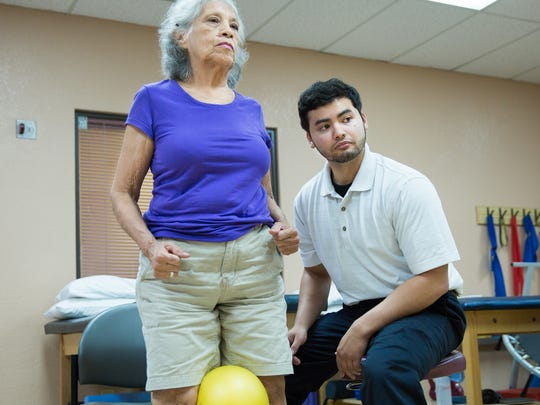 Southwest Sport & Spine Center employee Ray Cicchi, Physical Therapist Assistant,  right, and Urbana Clear look at a mirror to monitor the sit-to-stand ball squeeze exercise used to strengthen adductor muscles and straighten out knees.