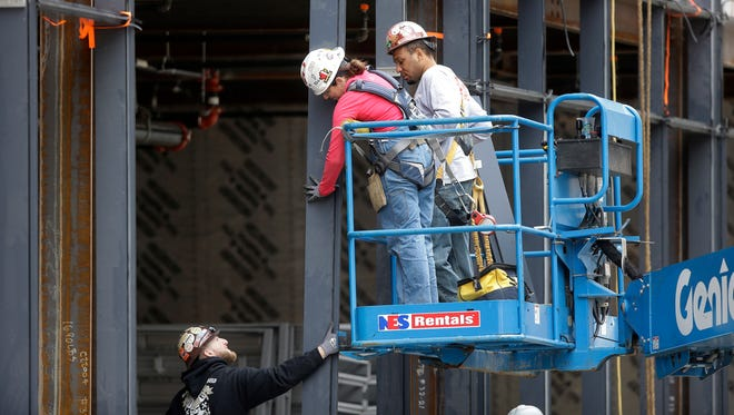 In this Thursday, May 19, 2016, photo, workers construct a building in Boston. On Friday, July 8, the U.S. government issues the June jobs report.