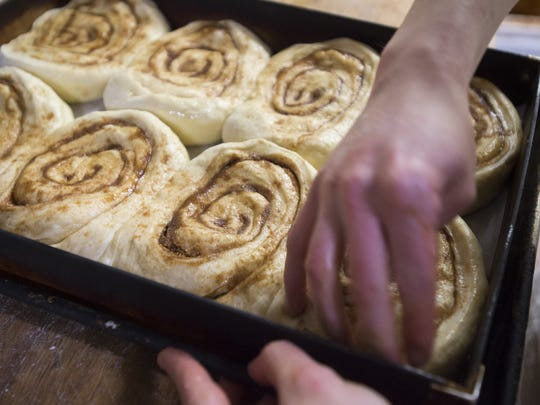 Cinnamon rolls are mashed down after they are placed in a pan for baking at Silver Grill Cafe.