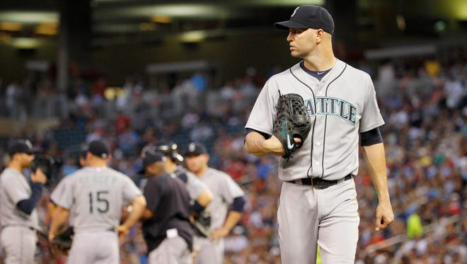 Seattle Mariners starting pitcher J.A. Happ leaves the mound after being replaced by Tom Wilhelmsen during the fourth inning of a baseball game against the Minnesota Twins in Minneapolis, Thursday, July 30, 2015.