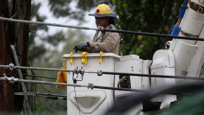 COT lineman Jonathan Wiley works to restore power after a tree knocked out lines on Mahan Road Monday.
