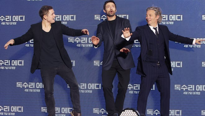Dexter Fletcher, right, shows off his best ski-jumping pose with with 'Eddie the Eagle' stars Taron Egerton, left, and Hugh Jackman at the film's  South Korean premiere in 2016.