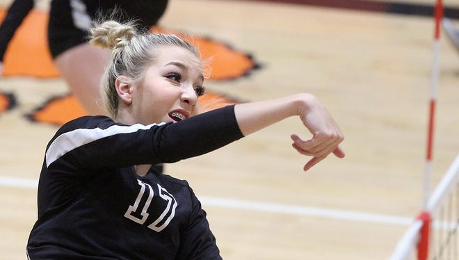 Aztec's Reigan Weaver gets a kill against Farmington on Saturday at Lillywhite Gym.