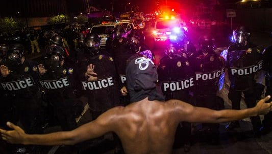 An activist throws out his arms as police stop marchers from continuing on Seventh Street on July 8, 2016, in Phoenix. The protester in the iconic photo was later identified as 17-year-old Devin Draper of Buckeye.