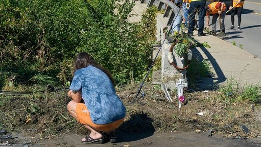 "Cindy Hartwick, mother of Deqouya Caroll, at the crash scene where her son died, while a 35th District Court work crew cleans the nearby bridge Sunday. ""It's horrible, horrible, horrible,"" Hartwick said Tuesday."