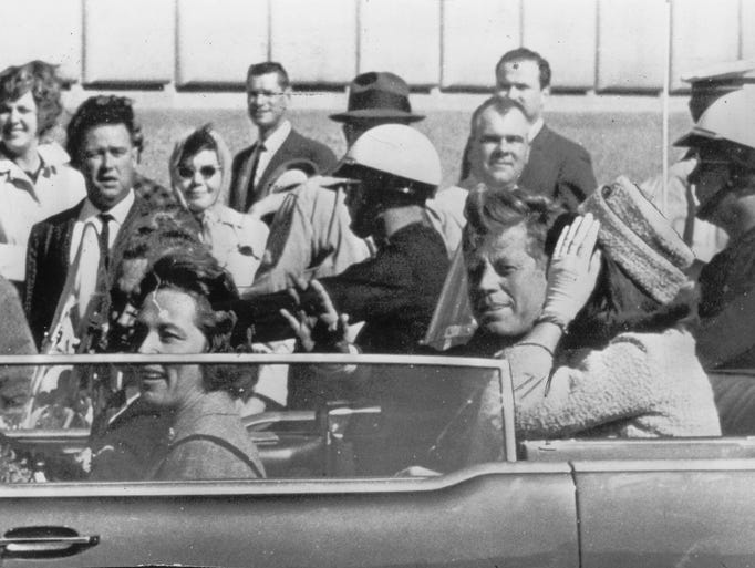 A smiling President Kennedy is shown riding in a Dallas, TX motorcade with Mrs. Kennedy only moments before he was shot and wounded fatally. (1963 File Photo)  President Kennedy in Dallas, moments before shooting.