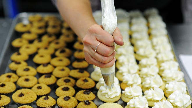 Michelle Smith frosts some mini cloud 9 cupcakes on Thursday, Dec. 18, 2014, at Oh My Cupcakes in Sioux Falls, S.D.