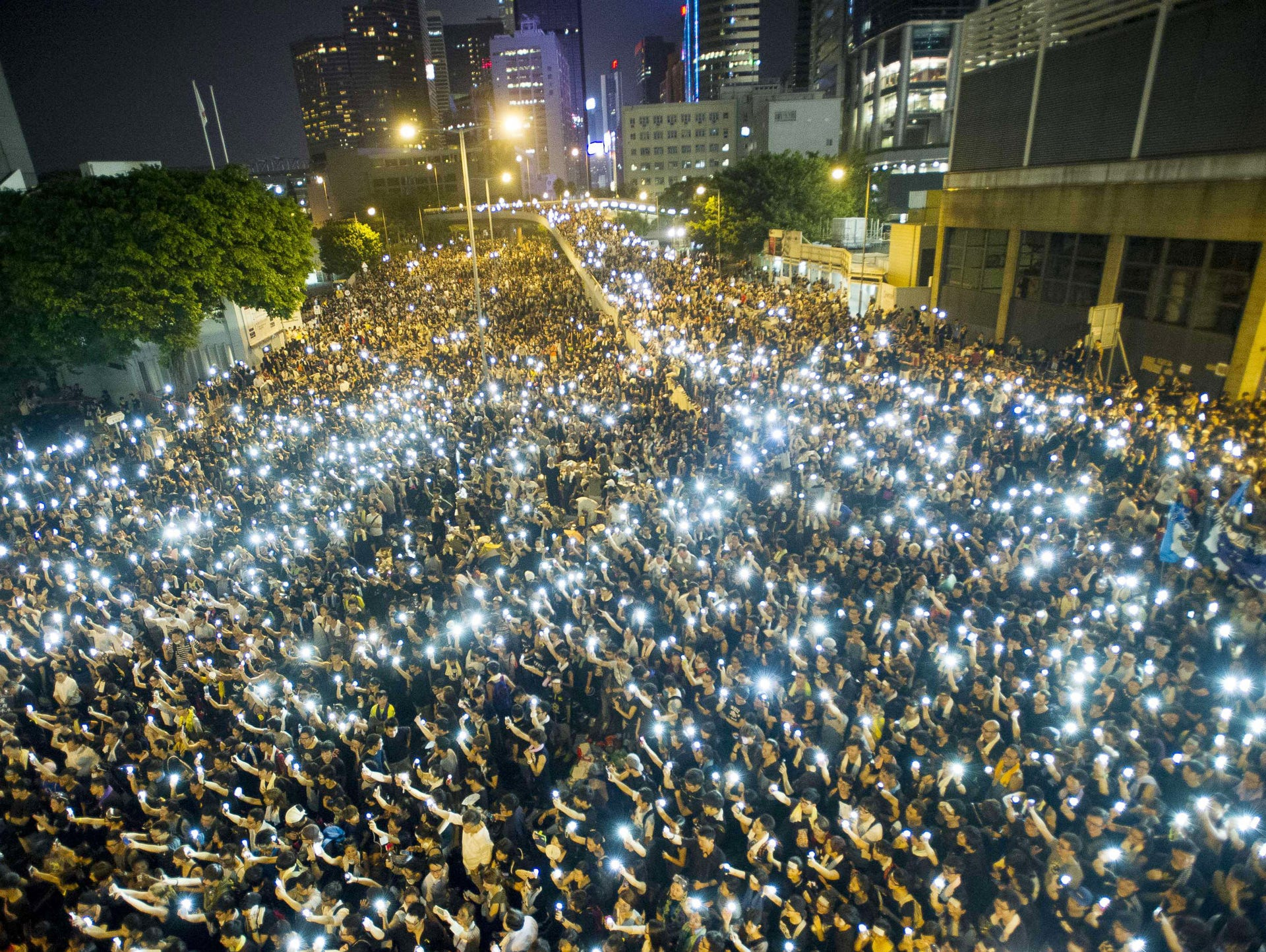 Protesters and student demonstrators hold up their cellphones in a display of solidarity during a protest outside the headquarters of Legislative Council in Hong Kong.