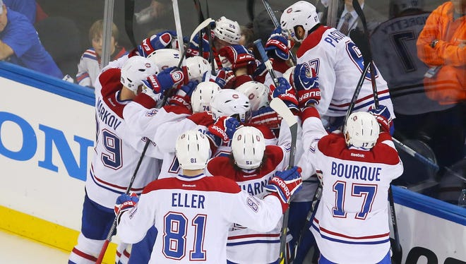 Montreal Canadiens center Alex Galchenyuk (27) celebrates with his teammates after scoring the game-winning goal against the New York Rangers during the overtime period in game three of the Eastern Conference Final of the 2014 Stanley Cup Playoffs at Madison Square Garden.