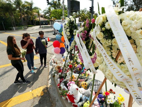 People pray before placing flowers at a sidewalk memorial