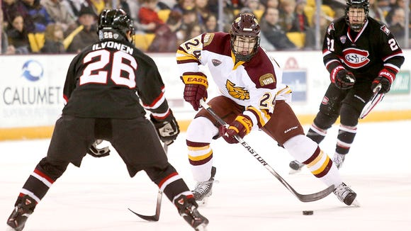 Charlie Sampair (24) of Minnesota Duluth skates with the puck through Mika Ilvonen (26) and Brooks Bertsch of St. Cloud State  during Friday's game at Amsoil Arena in Duluth. Minnesota Duluth defeated St. Cloud State 4-2.