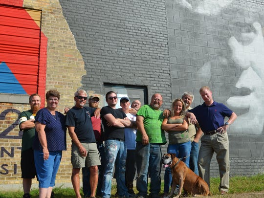 "Artists, city leaders and the community banded together to create the Red Arrow soldier mural on the side of Historic Richter Vinegar Plant. Pictured front row, from left: Deb Hardy, Ed Hansen, Jon Kuehn, Erin LaBonte and Manitowoc Mayor Justin Nickels; back row, from left: Chris Isherwood, David Carpenter, Jorge Tello, Bobby Jagemann, Scott Remaker and dog ""Vinny."""