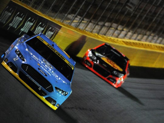 Brad Keselowski, driver of the #2 Detroit Genuine Parts Ford, races Tony Stewart, driver of the #14 Bass Pro Shops / Mobil 1 Chevrolet, during the NASCAR Sprint Cup Series Bank of America 500 at Charlotte Motor Speedway on October 11, 2014 in Charlotte, North Carolina.