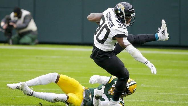 Jacksonville Jaguars' running back James Robinson gets past Green Bay Packers' cornerback Josh Jackson during the first half Sunday in Green Bay, Wisconsin.