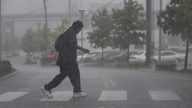 In this file photo, a pedestrian makes his way across 11th Ave. during pouring rain Thursday, June 15, 2017, in Nashville, Tenn.