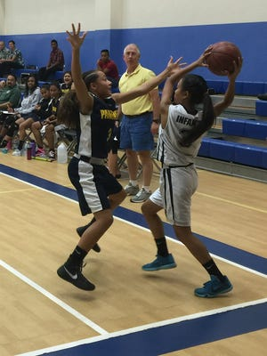 Guam High Panthers' Alexia Brown puts pressure on Harvest Eagles' Katrina Infante during the IIAAG girls basketball matchup on Nov. 16. The Eagles won 33-31 in overtime.