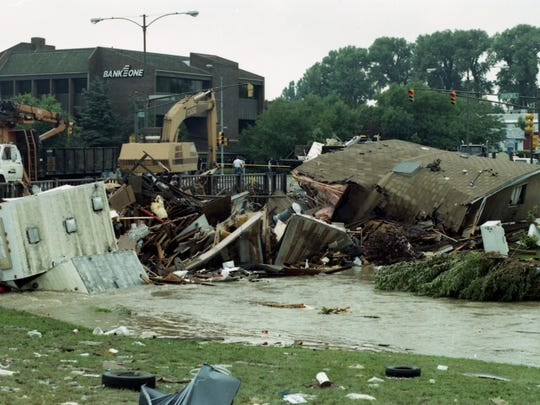 Trailers, vehicles and debris collect at the South College Avenue bridge over Spring Creek on July 29, 1997.