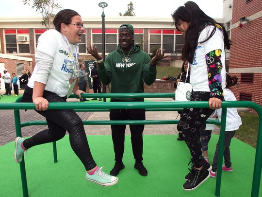 New York Jets linebacker Taiwan Jones helps Brianna Mejia, l, and Nicole Espinosa on the parallel bars as members of the New York Jets unveil a PLAY 60 Fitness Zone playground with 35 students from Dover Middle School as part of the NFLÕs 17th annual Hometown Huddle, an NFL-wide day of service with United Ways across the nation. October 20, 2015, Dover, NJ
