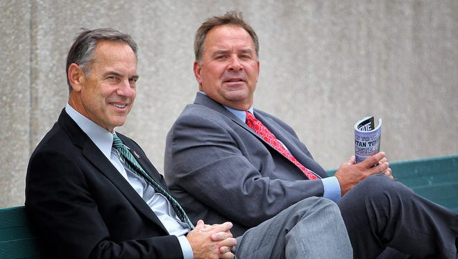 Michigan State football coach Mark Dantonio, left, and Indiana coach Kevin Wilson talk on sideline prior to a game at Spartan Stadium.