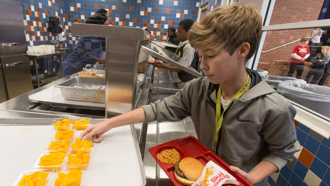An L.J. Alleman Middle student picks up lunch in the cafeteria Tuesday. A widespread network shutdown has hampered tasks at many schools, including lunch lines.