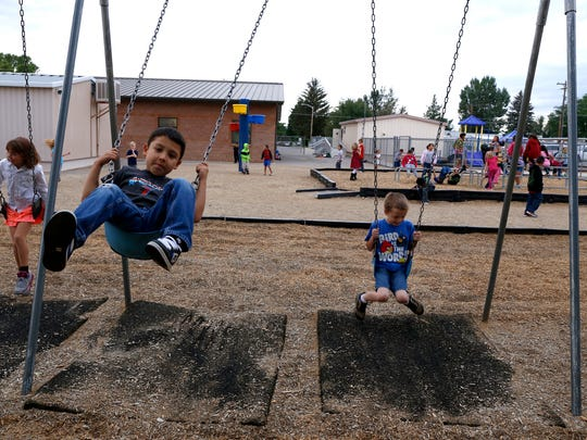 Second-graders Alex Espinoza, 7, left, and Tyer Shaw, 7, swing on the playground Sept. 3 before school begins at Lydia Rippey Elementary School in Aztec.