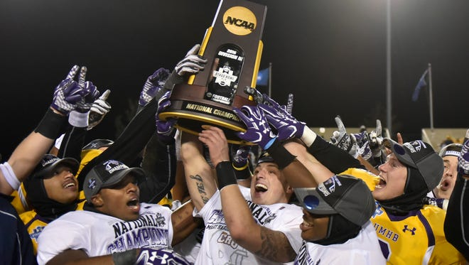 Mary Hardin-Baylor running back Duane Thompson (5), defensive back Jaedon Johnson (18), and safety Hunter Schmidt (6) lift the trophy following their victory against Wisconsin-Oshkosh at Salem Stadium in Salem, Va., Friday, Dec. 16, 2016.