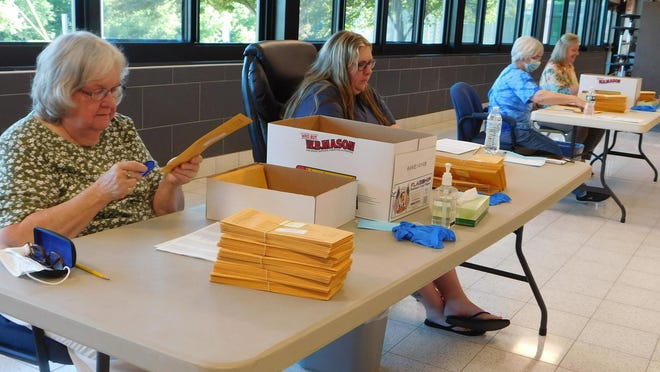 From left: Carol Ernye, Lacy Baylor, Donna Loucks and Jennifer Winkler open envelopes as they prepare to count ballots Tuesday in the James A. Green High School cafeteria in Dolgeville.