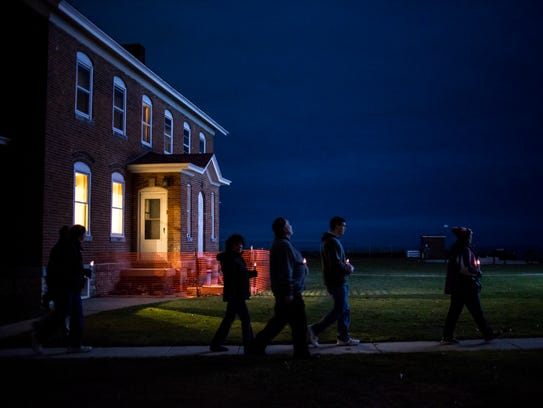 Participants walk to the lighthouse during a candlelight