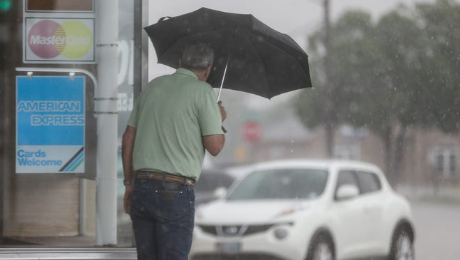 A man looks around the corner before heading to his car during a thunderstorm Friday, May 19, 2017, in San Angelo.