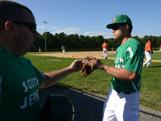 South Jersey Giants third baseman Tim Dezzi gets a fist bump from a coach after making an inning-ending play on July 9.