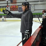 Milford hockey head coach Hugh Pobur talks to his players during the first day of tryouts.