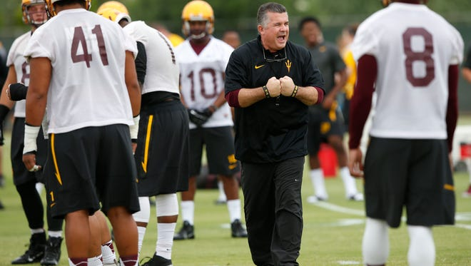 ASU coach Todd Graham instructs his team during morning practice at Kajikawa Practice Fields in Tempe on Aug. 1, 2014.