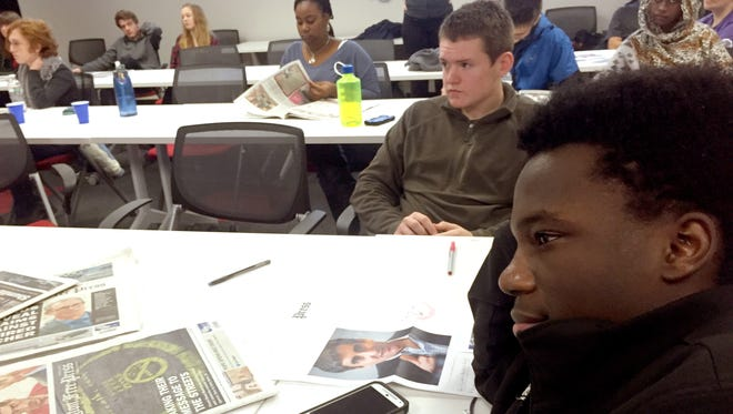 Right, Burlington High School junior Kenndy Irakoze listens as groups present the day's news in a front-page design workshop at the Burlington Free Press Tuesday.