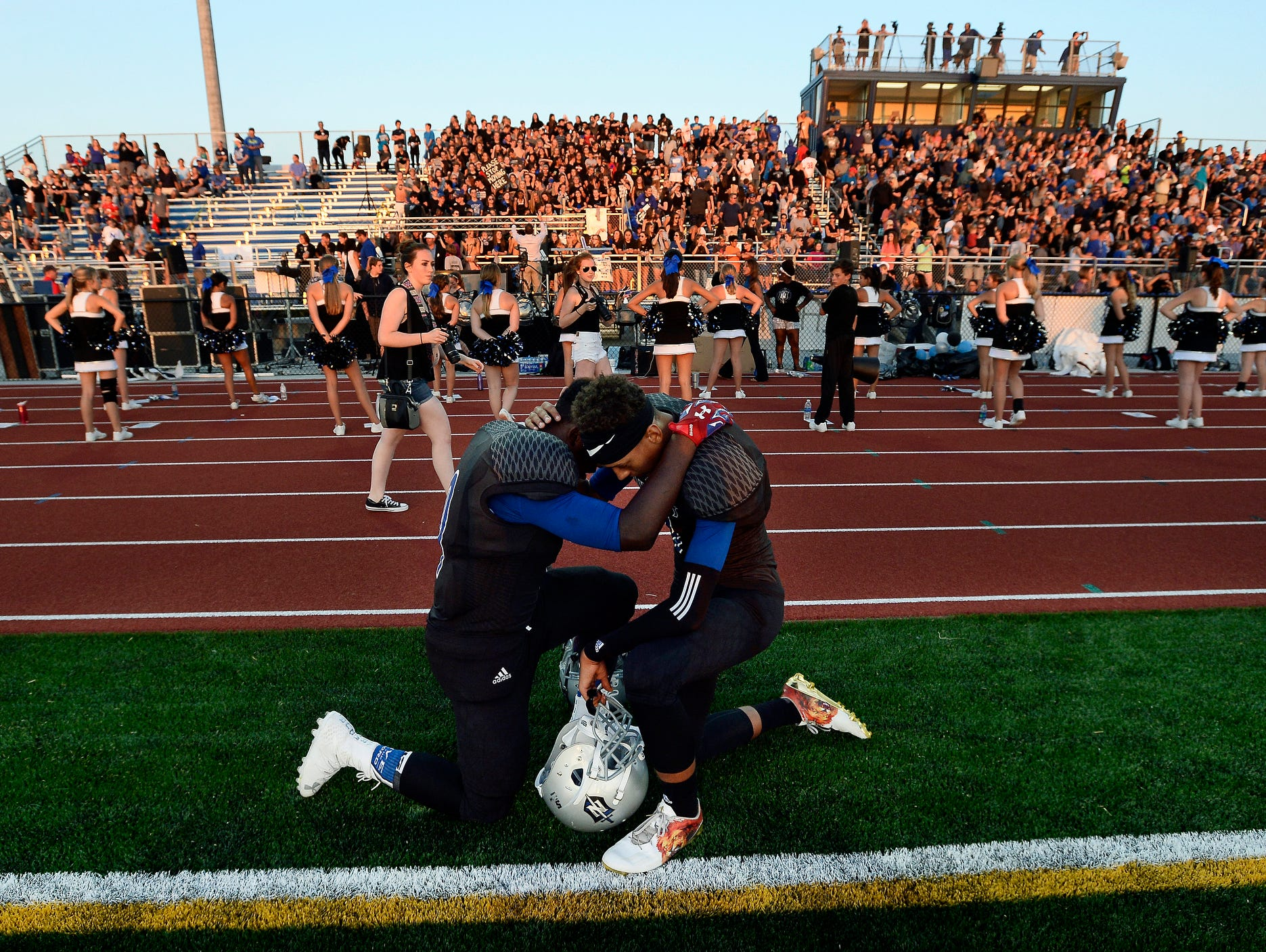 Nolensville running back Jy' Don Greene, left, and quarterback Brandon Wharton, right, pray before the start of the team's homecoming game against South Gibson High School on Friday, Sept. 2, 2016, in Nolensville, Tenn.