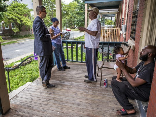 New Castle County executive candidate Matt Meyer (left) campaigns in Wilmington's Triangle neighborhood, talking with (from left) Barbara Johnson, Jerry Potter and Gary Potter, holding four-month-old daughter Paris Marie Potter, on June 27. Meyer secured the Democratic nomination Tuesday.